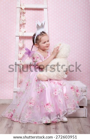 4 years old girl sitting on a wooden box . behind her pink background. holding toy - stock photo