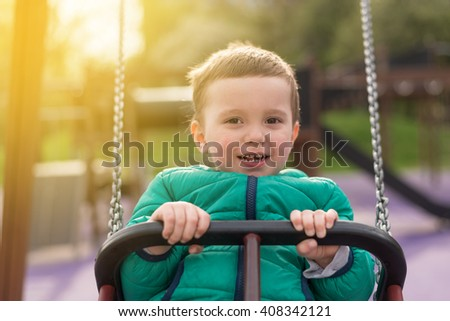 2 years old happy and smiling boy playing outdoors and swinging - stock photo