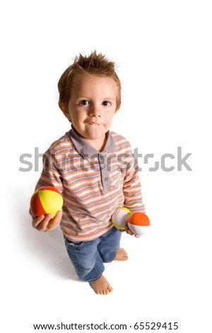 2 years old happy kid playing with balls. - stock photo