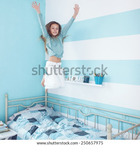 8 years old kid girl jumping on the bed at her room, square photo - stock photo