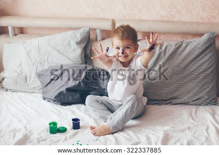 2 years old little boy dressed in pajamas is painting in the bed - stock photo