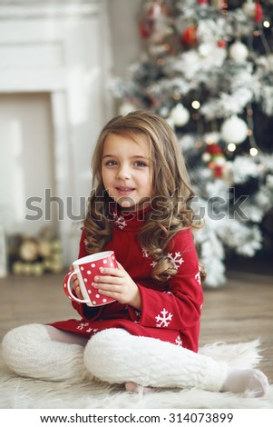 5 years old little girl drinking milk near Christmas tree in morning at home