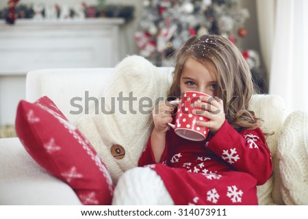 5 years old little girl sitting on cozy chair and drinking milk near Christmas tree in morning at home - stock photo