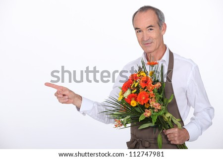 65 years old male florist taking a flowers bouquet and pointing finger on something - stock photo