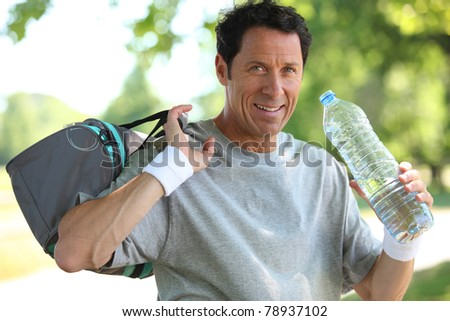 50 years old man drinking man after he did sport - stock photo