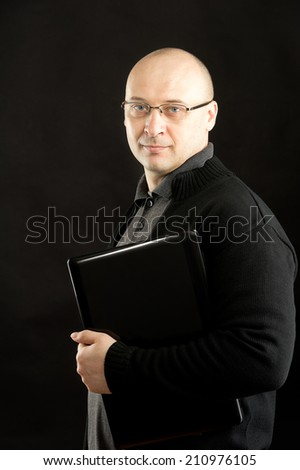 38 years old man holding black notebook wearing black jacket and glasses  - stock photo