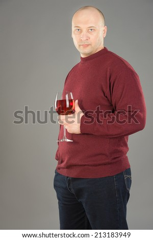38 years old man holding Rose wineglass, man wearing  red sweater and dark blue jeans - stock photo