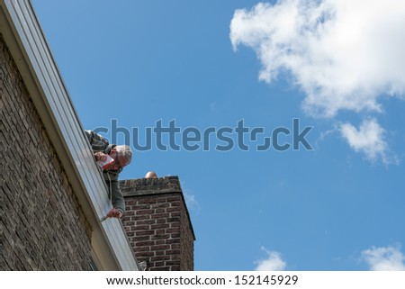 60 years old man on the roof of his house is painting the fascia - stock photo