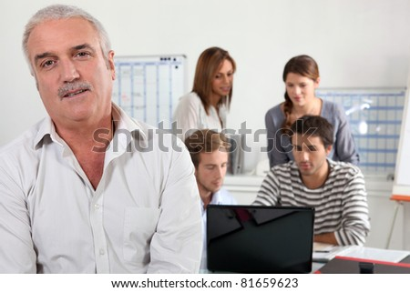 55 years old man watching us and  four young people focused on a laptop - stock photo