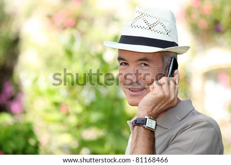 65 years old man wearing a straw hat and phoning - stock photo