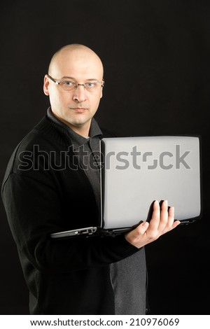 38 years old man working on notebook wearing glasses and black jacket  - stock photo