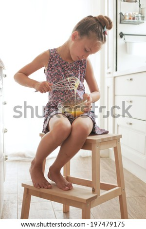 7 years old school girl cooking on the vintage kitchen, casual lifestyle photo series - stock photo