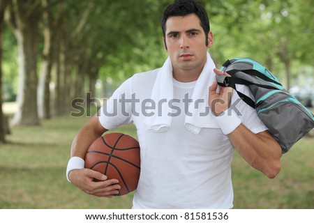 30 years old sportyman holding a basket ball and a sports bag - stock photo