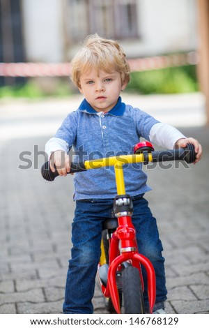 2 years old toddler boy learning to ride on his first bike