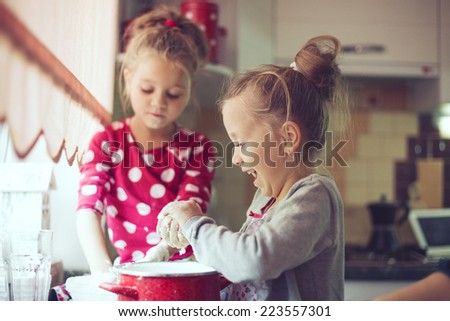 5 years old twins cooking holiday pie in the kitchen, casual lifestyle photo series in real life interior - stock photo
