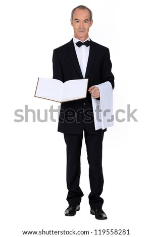 60 years old well dressed waiter is presenting a visitor book or a menu - stock photo