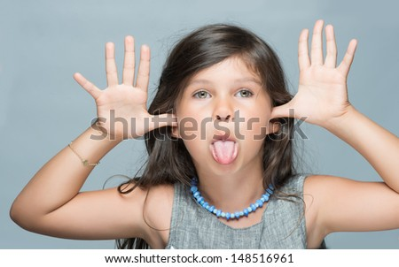 6 years old with funny expression and sticking tongue out - stock photo