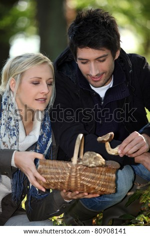 30 years old woman and man picking mushrooms - stock photo
