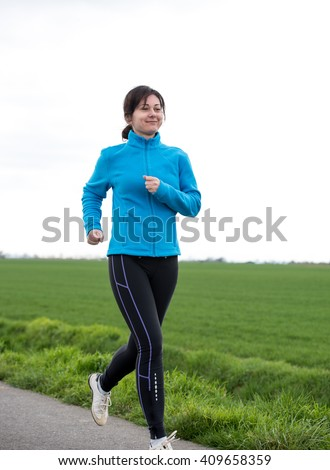 40 years old woman jogging (running) outside - stock photo