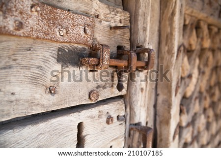 600 years old wooden doors with metal frame work and lock - stock photo