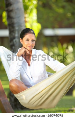 20-25 years woman portrait relaxing on hammock at exotic surrounding - stock photo