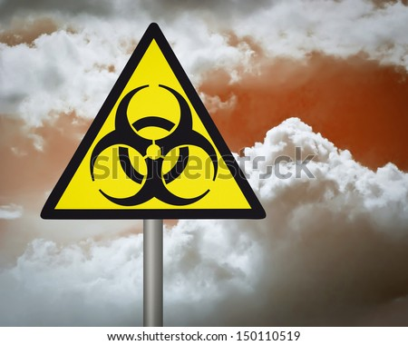 Yellow biohazard warning sign on against dark cloudy sky. - stock photo