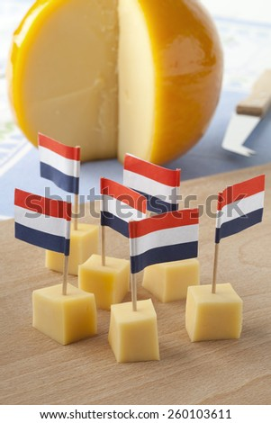 Yellow Edam cheese blocks with Dutch flags as a snack - stock photo