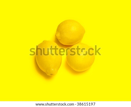 3 yellow lemons isolated on a yellow background.