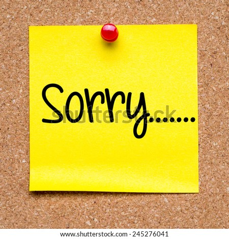 Yellow note with sorry. Blank yellow sticky note with sorry ... pined on a cork bulletin board. - stock photo