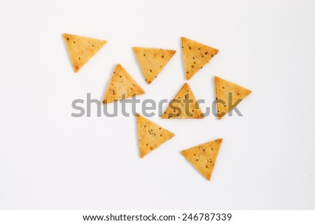 Yellow triangular crackers with poppy seeds, isolated on white background, closeup  - stock photo