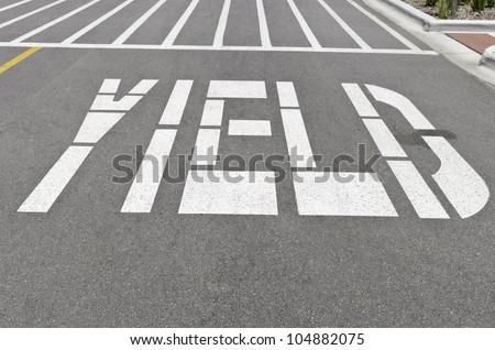 """Yield"" painted in white capital letters on pavement"