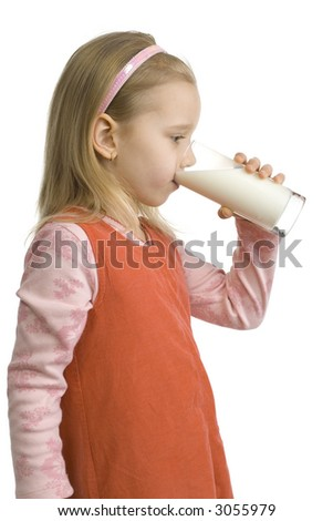 5-6yo girl standing and drinking glass of milk. Side view. Isolated on white in studio.