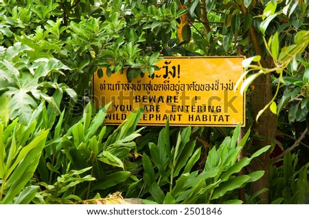 """You are entering elephant habitat"" sign surrounded by jungle foliage"