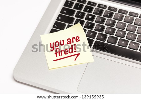 """you are fired"" written on sticky note, on laptop keyboard. - stock photo"