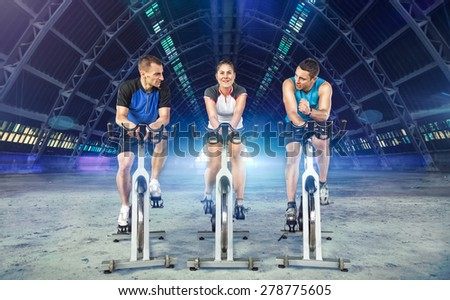 young active people riding exercise bikes - stock photo