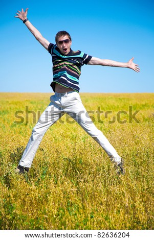 young adult man jump into the air in the autumn field - stock photo