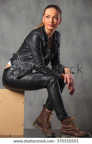 young attractive blonde rocker in leather posing smiling seated on a box, while looking away - stock photo