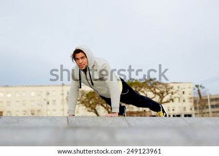 Young attractive man dressed in sweatshirt doing push ups outdoors at early morning - stock photo