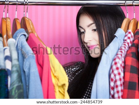 Young attractive surprised woman searching for clothing in a closet  - stock photo
