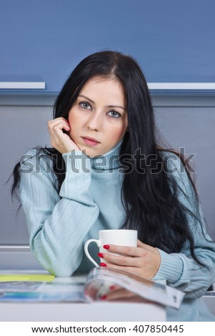 Young beautiful black hair woman in blue shirt drinking coffee and reading magazine in kitchen in morning  - stock photo