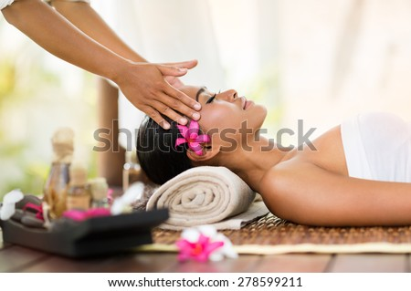 young beautiful Indonesian woman getting recreation massage of head - stock photo