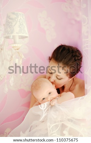 Young beautiful mother kissing her small sleeping newborn baby - indoors - stock photo