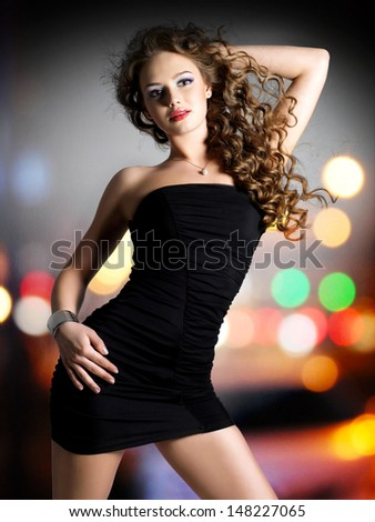 Young beautiful woman in black dress poses over night lights - stock photo