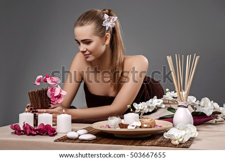 young beautiful woman in spa environment. The girl relaxes in the spa salon.  empty space for your ad text.