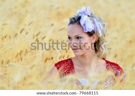 young beautiful woman on golden cereal field in summer