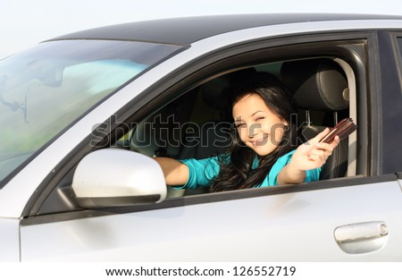 young brunette girl behind the wheel driving displays documents - stock photo