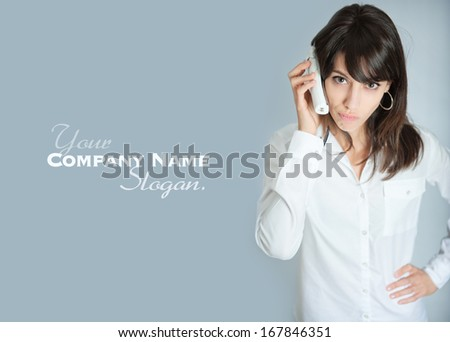 Young brunette talking on the phone with an annoyed expression  - stock photo