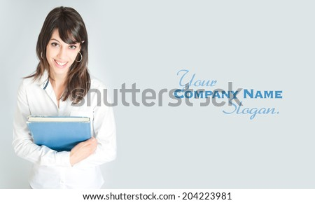 Young brunette wearing a white shirt holding a book  - stock photo