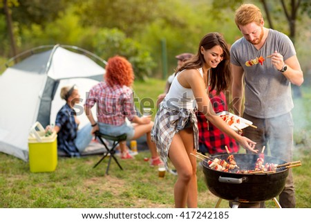 Young brunette with boyfriend serving on plate barbecue to their friends in campground - stock photo