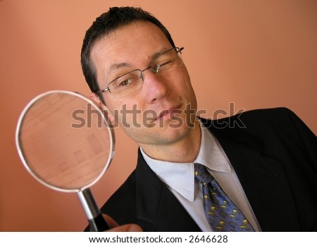 young businessman looks to chart through a magnifying glass . - stock photo